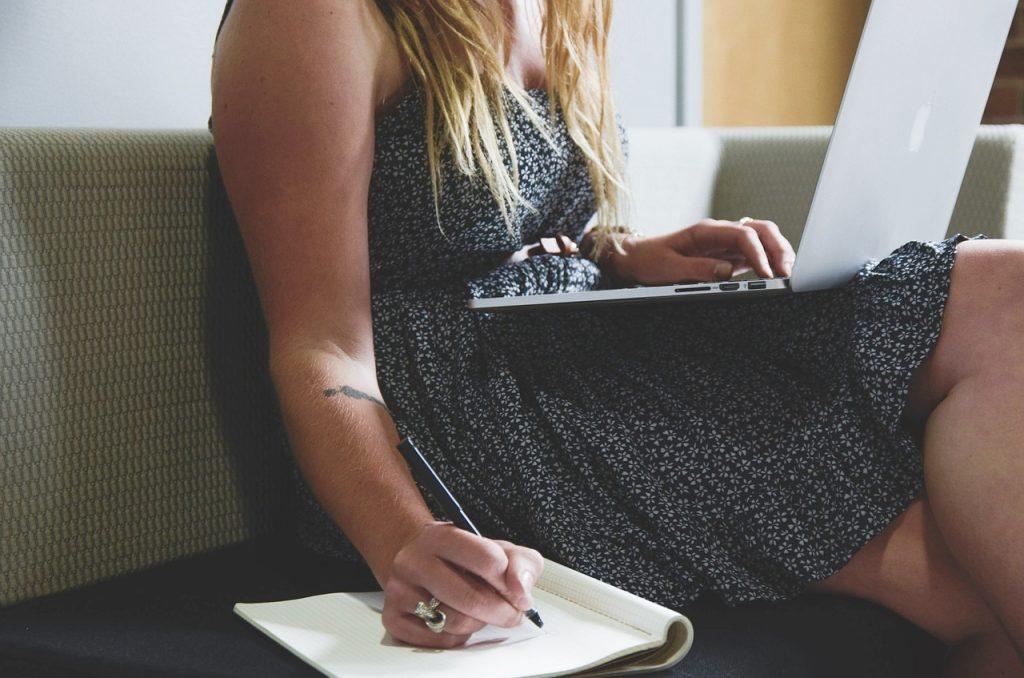 Vaalea nainen kannettava tietokone polvillaan kirjoittaa muistikirjaan.