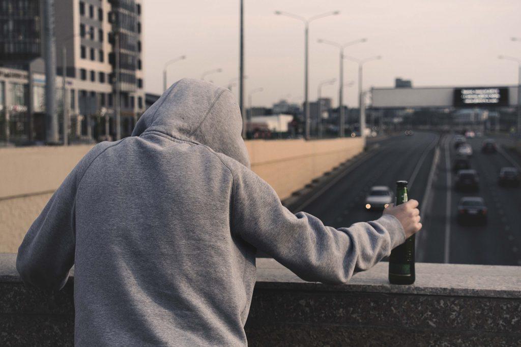 Nuori huppupäinen tyyppi sillalla, selkä kameraan päin, pullo kädessä, katsomassa ohi ajavia autoja.