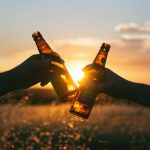 Kahden olutpullon kilistelyä ilta-auringossa pellon laidalla