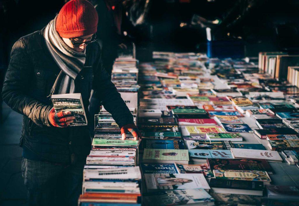Kirjojen kirpputori, jonka kirjoja selailee mies puneinen pipo päässä.
