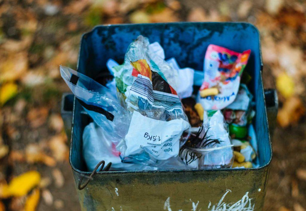 Melkein täynnä oleva roskakori syksyisessä maisemassa.