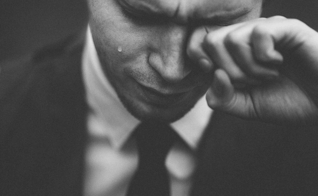Pukupäinen itkevä nuori mies mustavalkoisessa kuvassa