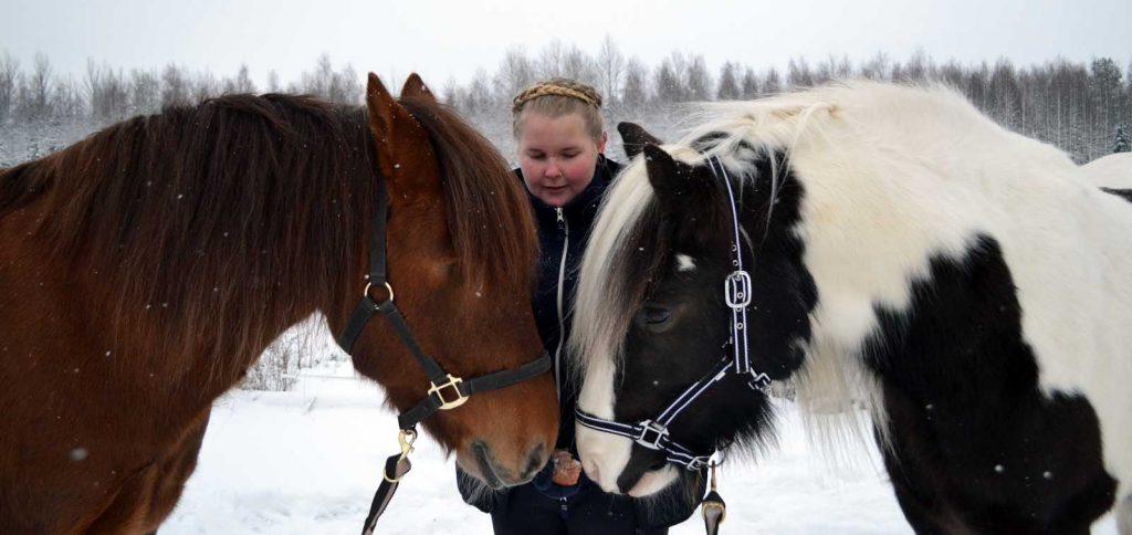 Kaksi hevosta turvat vastakkain, joiden takana blogin kirjoittaja Neea hevosia syöttämässä.