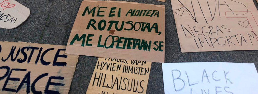 Mielenosoitus-kyltti, jossa teksti: Me ei aloiteta rotusotaa, me lopetetaan se.