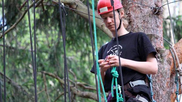 Mikael nojailee mäntyyn korkealla puussa ja katselee käsissään olevaa köyttä.