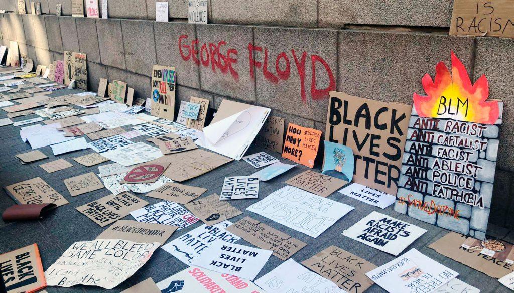 Kymmeniä rasismin vastaisia kylttejä levitettynä kadulle ja seinää vasten