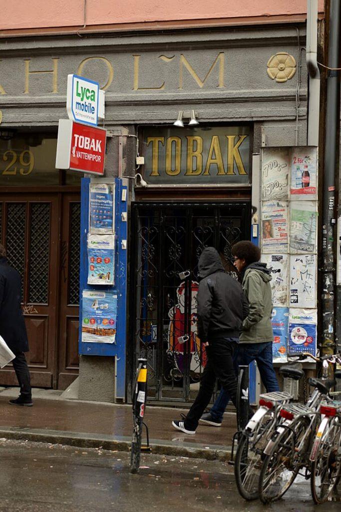 Tukholmalainen kadun varrella oleva tupakkakauppa, jonka ohi kävelee kaksi ihmistä.