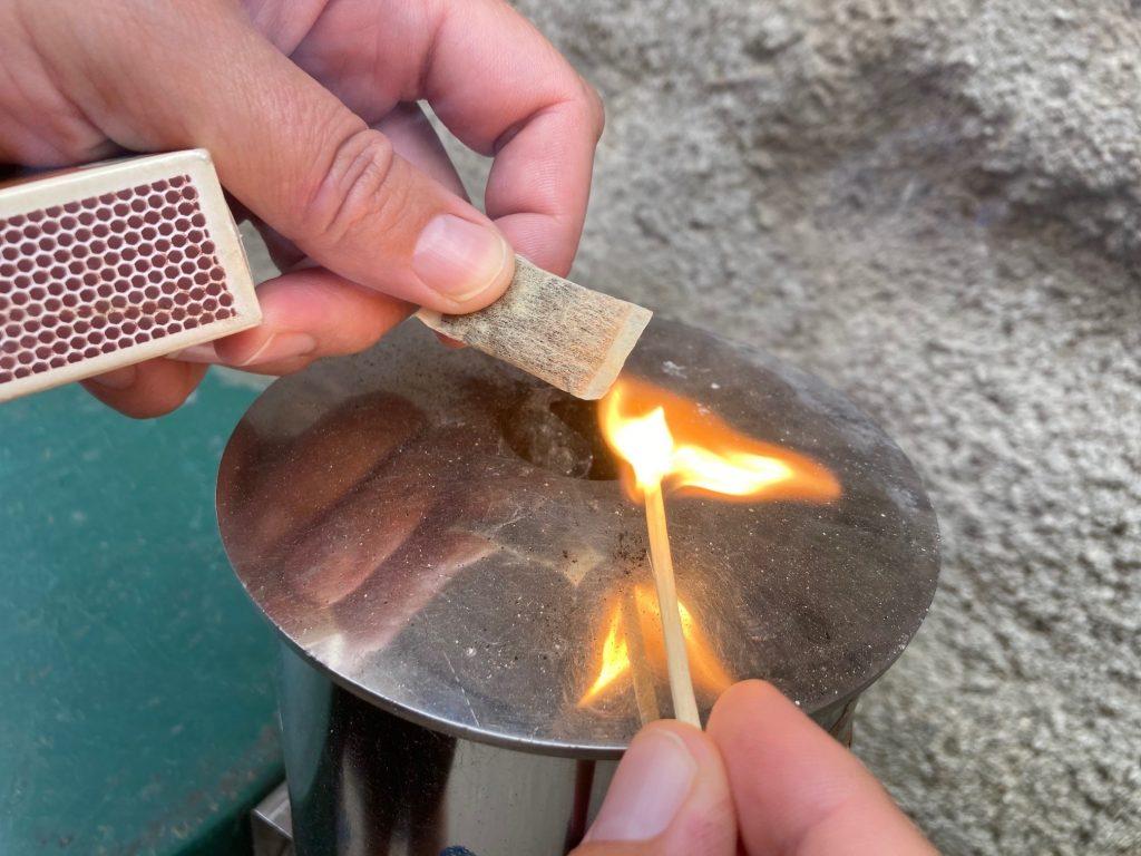 Nuuskapussia yrtitetään sytyttää tulitikulla.